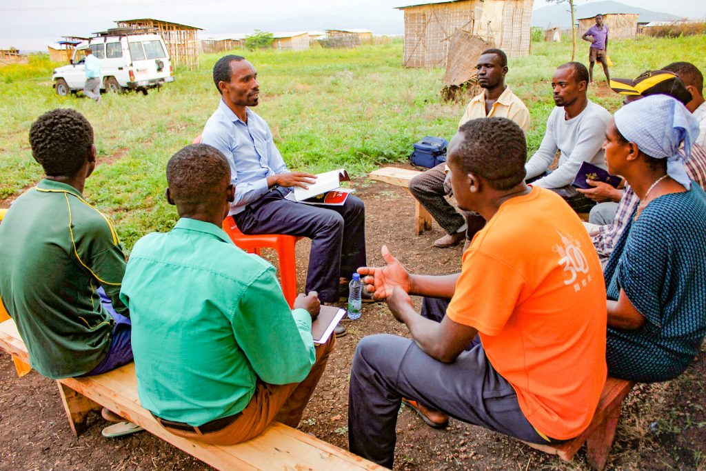 Man leading a bible study in a village setting